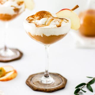 Two ice cream floats with caramel sauce and apple slices against white background