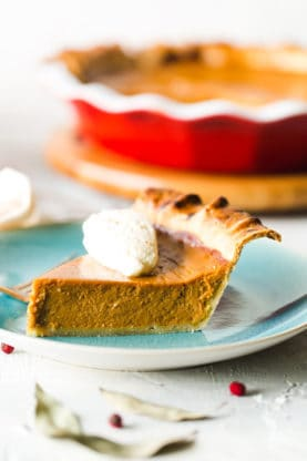 Close up of a slice of sweet potato pie sitting on a light blue plate with a dollop of whip cream on top of the pie.