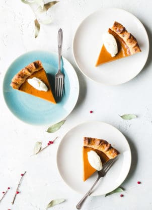 Three slices of sweet potato pie sitting on their own plates. Two plates are white, and one plate is light blue in color.