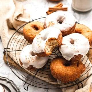 A stack of cider donuts piled high with one glazed and biten into ready to serve against marble background