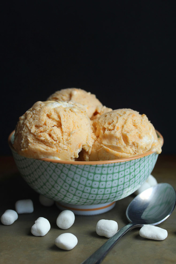 A bowl of sweet potato ice cream scoops with spoon and marshmallows in background
