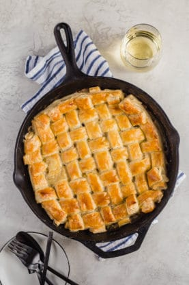 An overhead shot of a cast iron skillet filled with baked Easy Chicken Pot Pie Recipe with lattice puff pastry crust