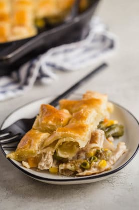 A plate of homemade chicken pot pie recipe and fork ready to be served with easy pot pie in background