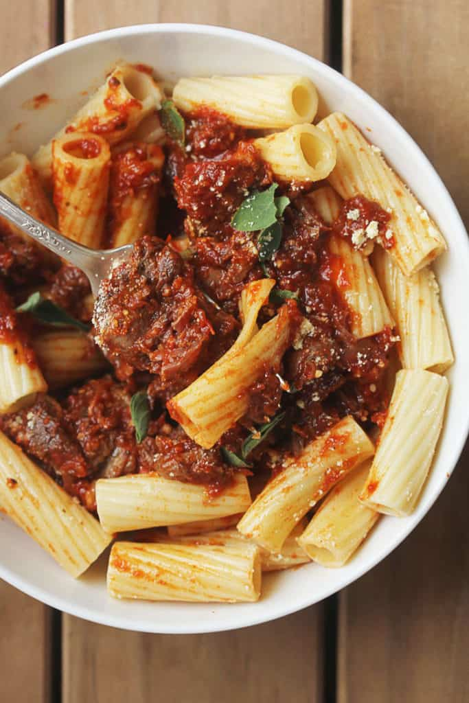 Italian pot roast in thick bolognese sauce recipe and rigatoni ready to eat with fork pierced through pasta