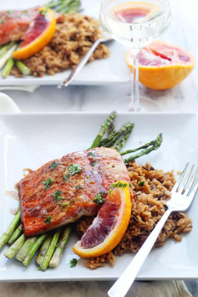 Two plates of orange honey glazed salmon over asparagus and rice with wine ready to serve