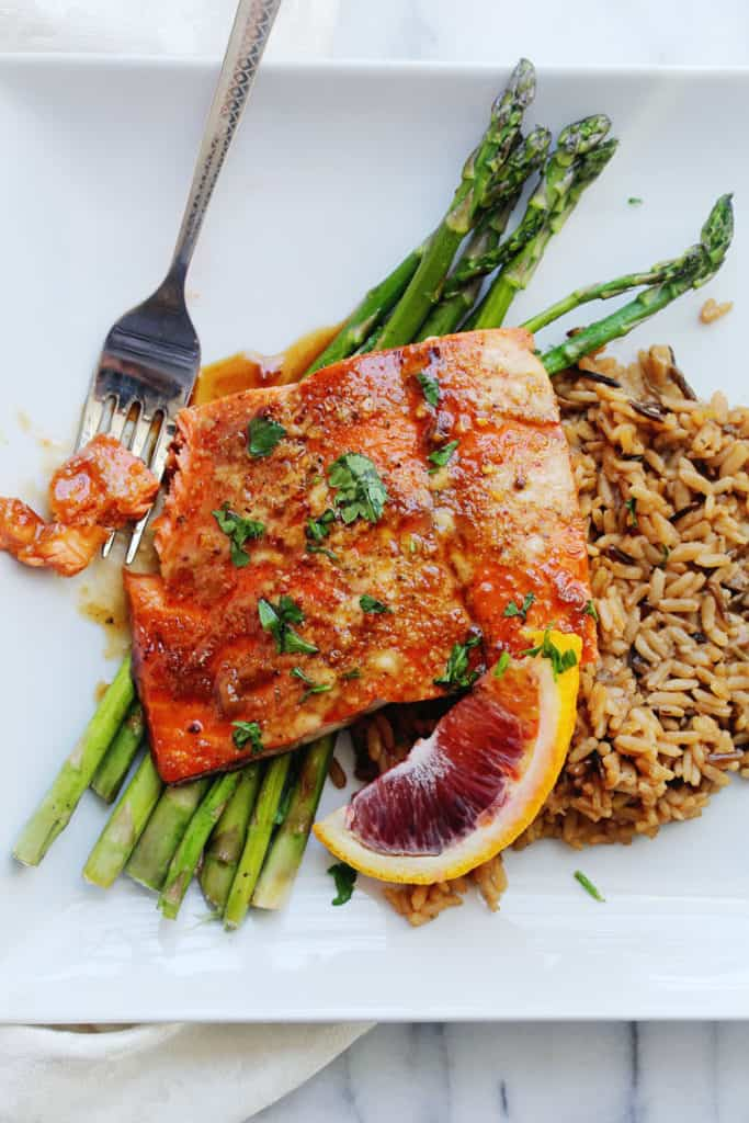 An overhead of orange honey glazed salmon recipe with sauce over rice and asparagus ready to serve with fork