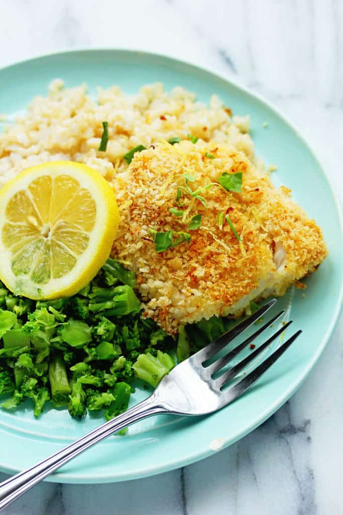 Lemon Panko Crusted Fish surrounded by rice and broccoli pieces. It's an awesome breaded fish recipe.