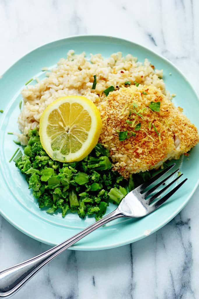 Lemon Panko Crusted Fish surrounded by rice and broccoli pieces. It's seriously one of the best healthy fish recipes ever!