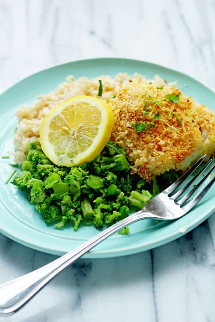 Baked Cod with Panko surrounded by rice and broccoli pieces.