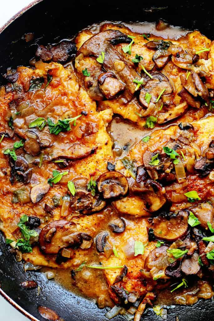 A overhead shot of a Healthy Chicken Marsala recipe in a skillet with mushrooms simmering away