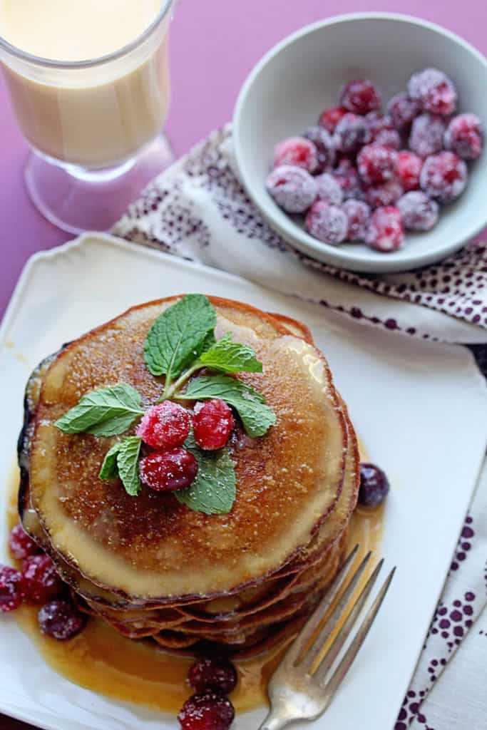Overhead shot of gingerbread pancakes topped with eggnog syrup, fresh mint and cranberries sitting on a white plate with a fork next to it.