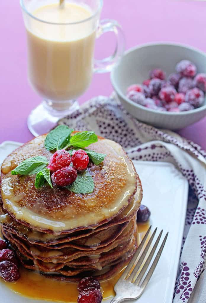 Gingerbread Pancakes with Eggnog Syrup topped with cranberries and mint as a garish sitting on a white plate next to a cup of eggnog and a bow of cranberries.