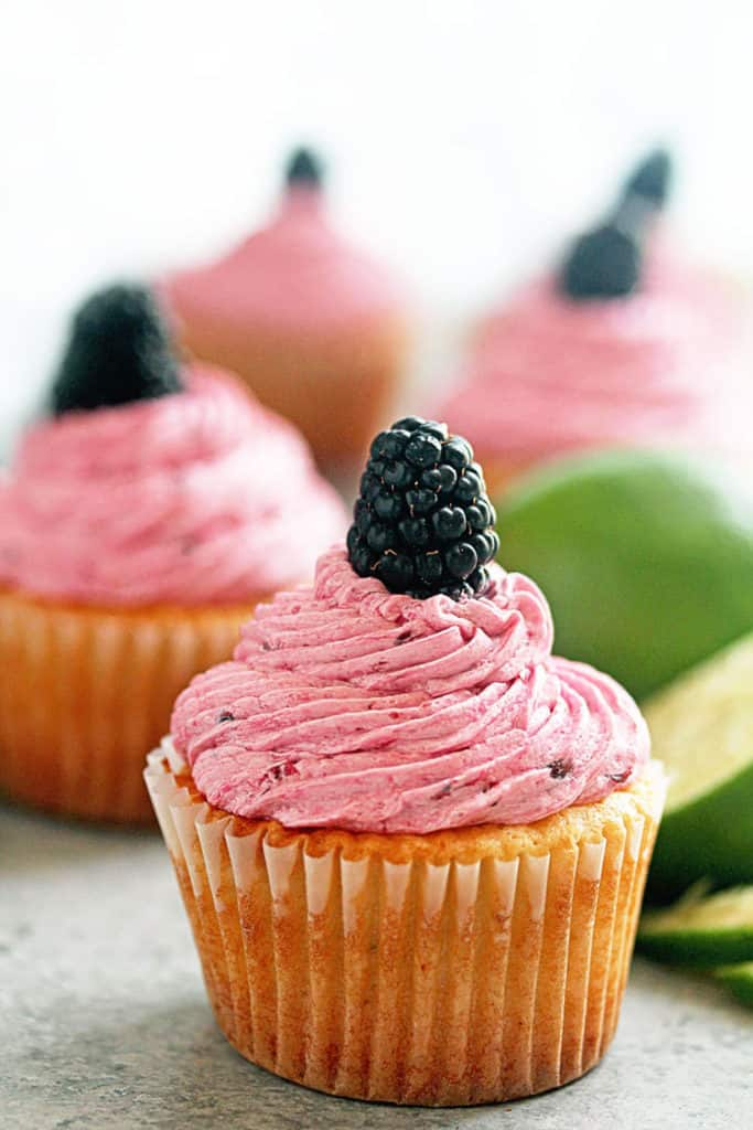 Close up of a blackberry lime cupcake topped with blackberry buttercream and one fresh blackberry.
