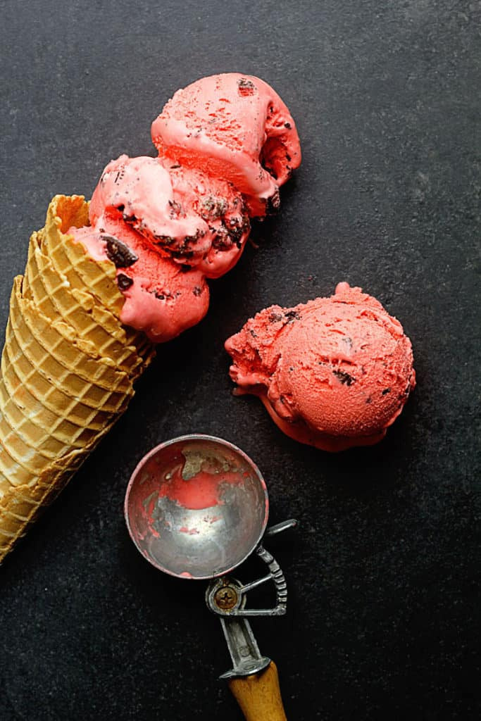 Oreo Red Velvet Ice Cream Recipe displayed with three scoops in a waffle cone and one scoop on the side next to it.