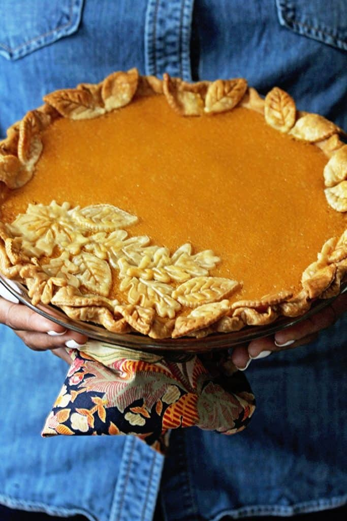 Hands holding decorated Sweet Potato Chess Pie ready to serve