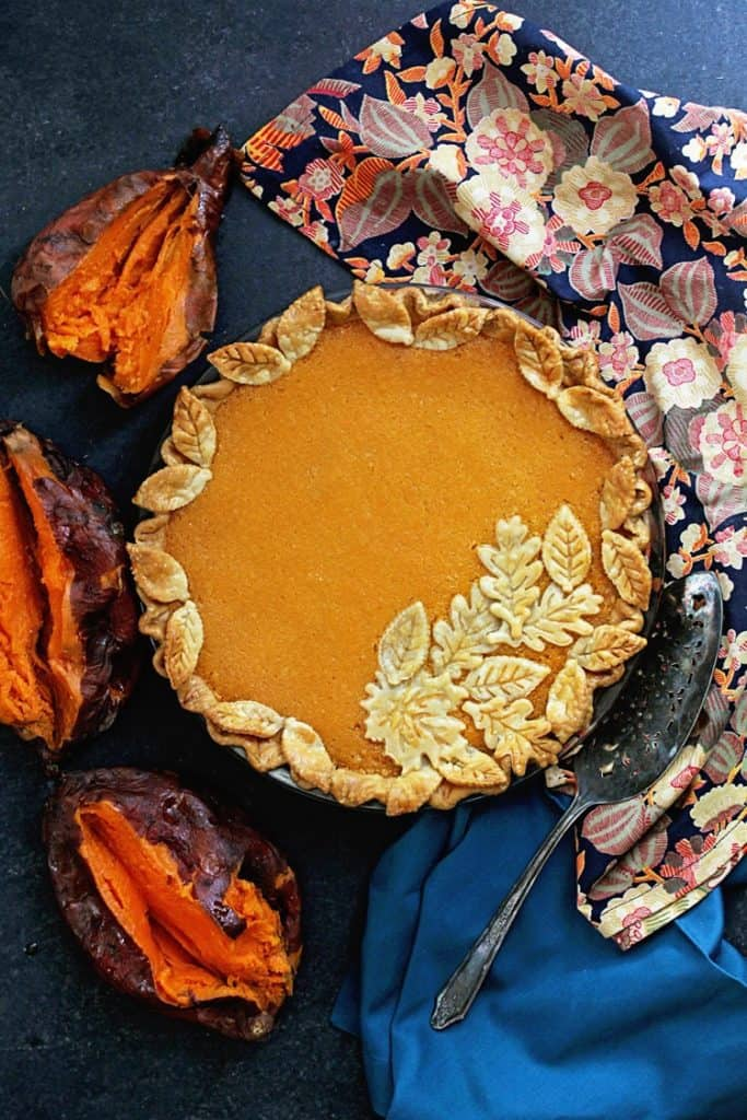 An overhead of a beautifully decorated sweet potato chess pie with roasted sweet potatoes and napkins surrounding it