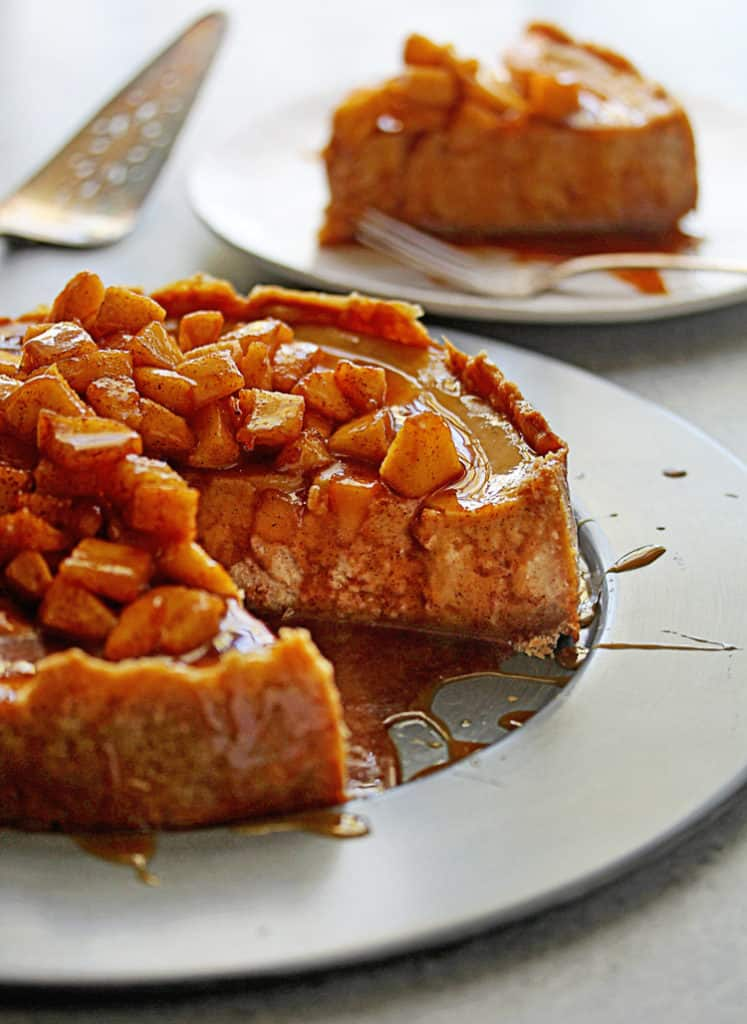 A decadent apple cheesecake with slice taken out on white plate with caramel sauce poured over it