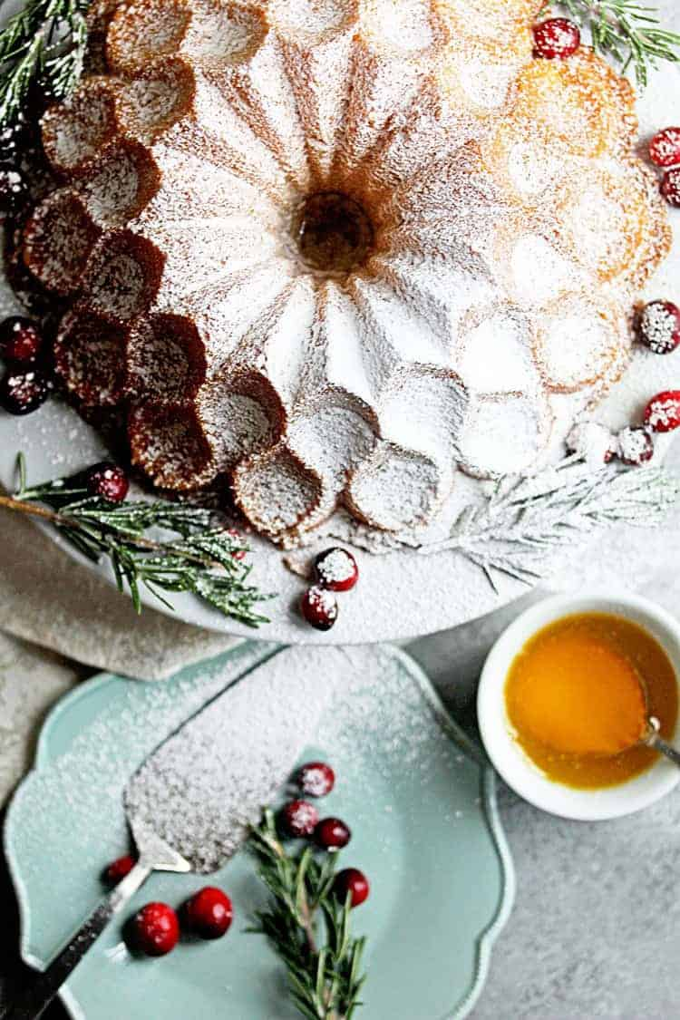 Overhead view of the Buttered Rum Eggnog Cake Recipe (Eggnog Pound Cake) topped with powdered sugar sitting on a white plate with cranberries and pine tree twigs around it. There is a fancy pound cake pan and a small bowl of melted butter by the cake.