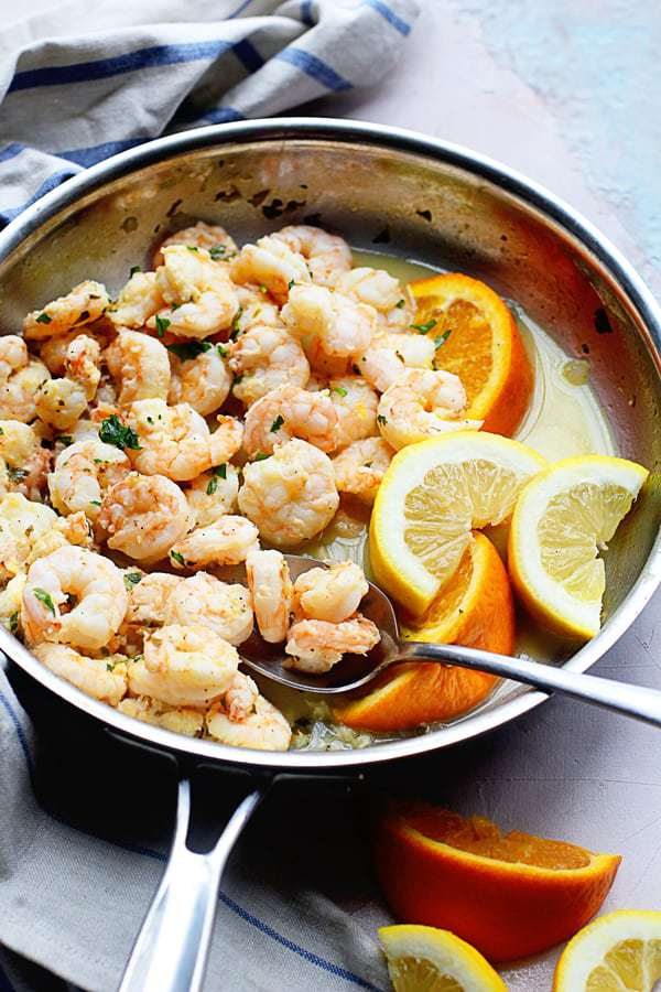 Citrus Shrimp Recipe contained in a frying pan with orange and lemon slices.
