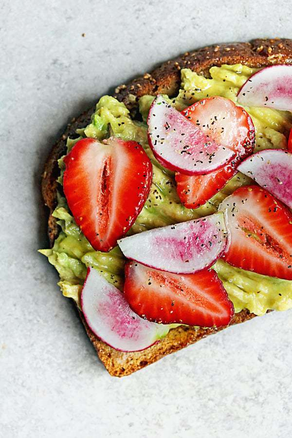 Learn how to make avocado toast; this photo depicts avocado toast topped with strawberries.