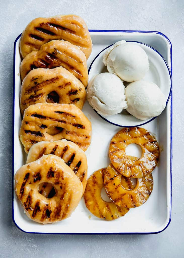Overhead of Grilled Pineapple slices and grilled donuts with vanilla ice cream on a white tray
