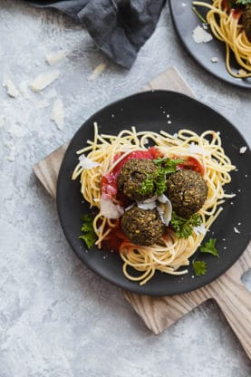 Spaghetti and Lentil Meatballs sitting on a black plate under a wooden cutting board.