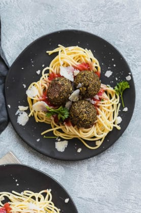 Learn how to cook lentils with this spaghetti and lentil meatballs recipe sitting on a black plate.