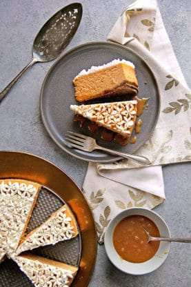 An overhead shot of a large sweet potato cheesecake with slices on a gray plate and a server and caramel sauce ready to pour over