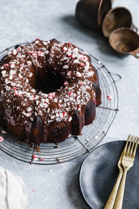 Chocolate Pound Cake recipe with Peppermint Ganache Glaze ready to serve with plates and forks against gray background