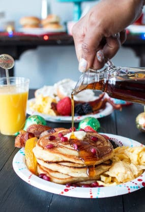 Orange Pancakes on plate with eggs and bacon with maple syrup being poured on top