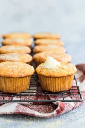 These moist, sweet and perfect corn muffins recipe is  stacked on a wire rack under a red and white napkin