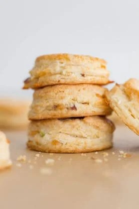 A stack of Cheddar Biscuits with bacon with crumbs surrounding