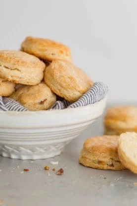 A large white bowl filled with Cheddar Biscuits overflowing ready to serve
