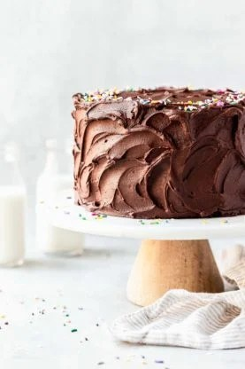Chocolate frosting on a birthday cake on a cake stand against white background