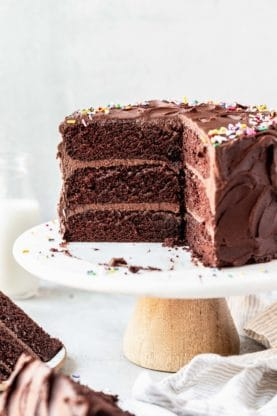 A sliced into chocolate birthday cake on white cake stand