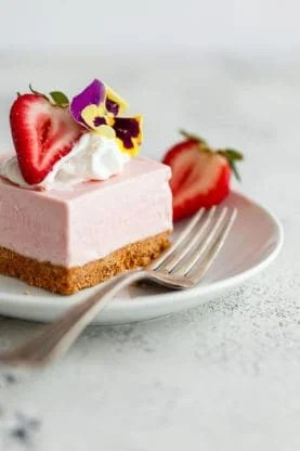 No Bake Strawberry Cheesecake Recipe - The easiest and most delicious strawberry cheesecake bars fit for any celebration. The filling is absolutely sensational and tastes just like strawberry ice cream. Addictive! This Easy Cheesecake recipe is ready to make you a believer!