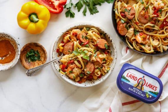 A large bowl of jambalaya pasta next to cajun spice blend and peppers and large skillet of jambalaya recipe
