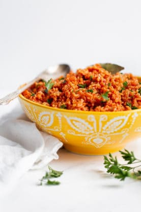 Jollof Rice Recipe served in a yellow bowl against white background