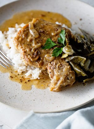 A smothered pork chop swimming in pork chop gravy on white plate with whit rice and greens