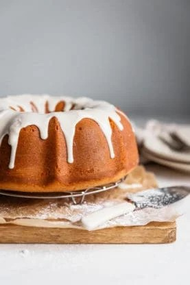 A whole Sour Cream Coffee Cake flavored with sweet potato topped with maple glaze against white background