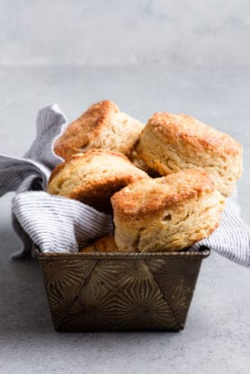 Rusted container filled with fluffy sour cream biscuits over gray napkin