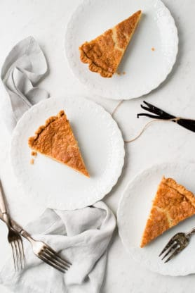 Overhead of buttermilk pie on three white plates