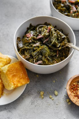 Side shot of a white bowl filled with Collard Greens with hamhock against gray background with cornbread