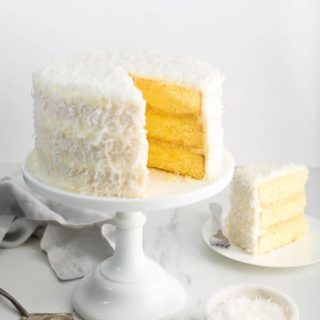 Pineapple Coconut Cake recipe on white cake stand with slice of cake on white plate against white background