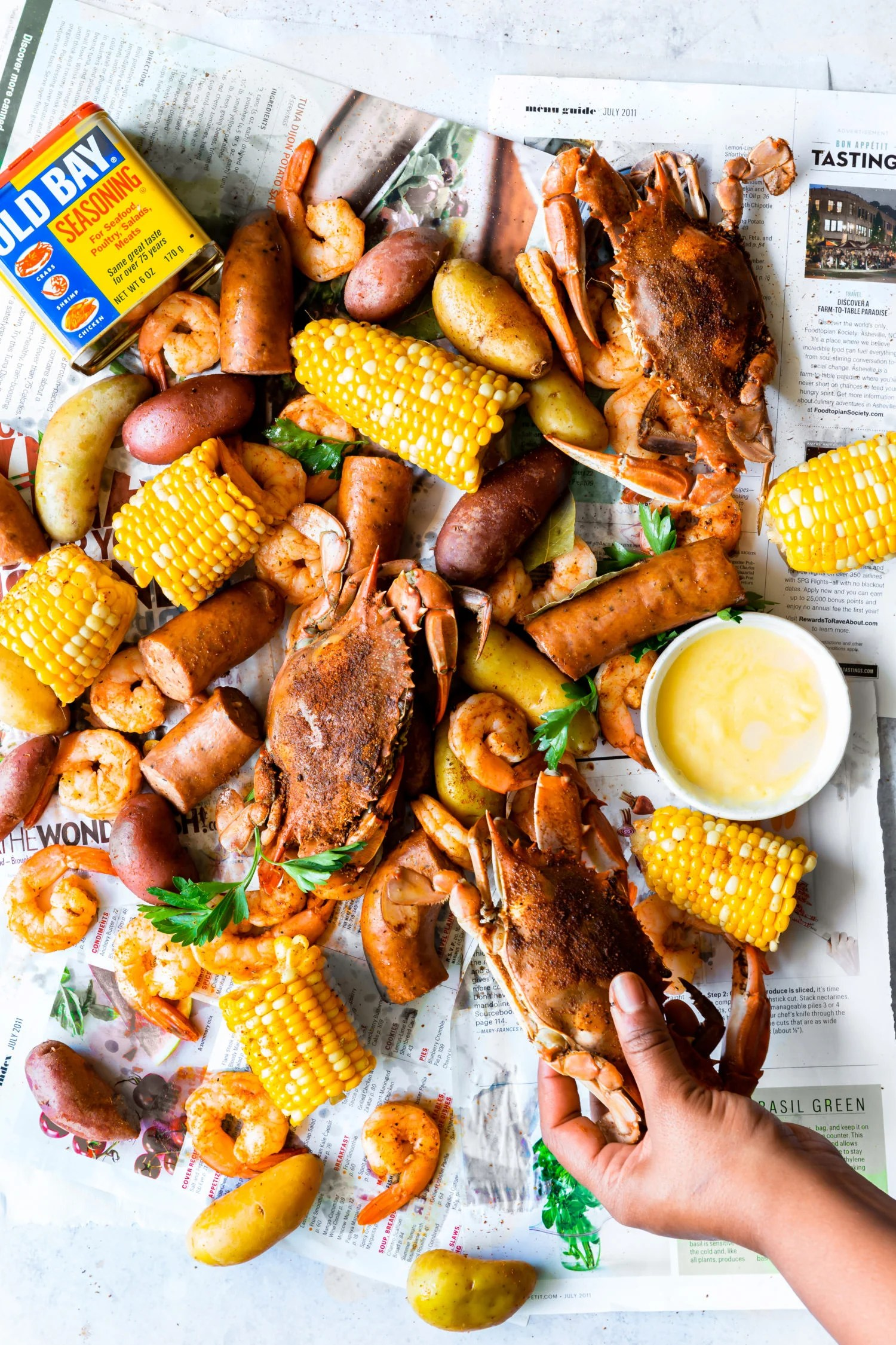 Labor Day Recipes - Overhead shot of hand picking up blue crab at low country boil gathering