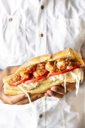 Close up photo of hands holding a New Orleans Shrimp Po' Boy