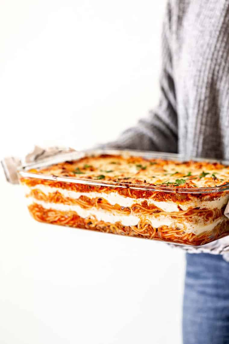 Woman holding delicious baked spaghetti recipe in hands
