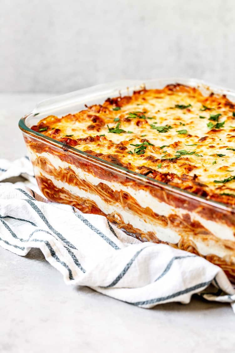 A large Pyrex tray of baked pasta dish with bubbly cheese