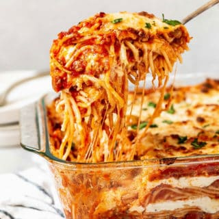 A large spoon lifting Millionaire Baked Spaghetti with delicious layers