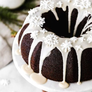 A close up of Gingerbread bundt cake with white glaze on white cake plate